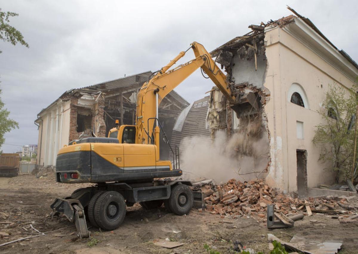 Żółta koparka w trakcie burzenia budynku