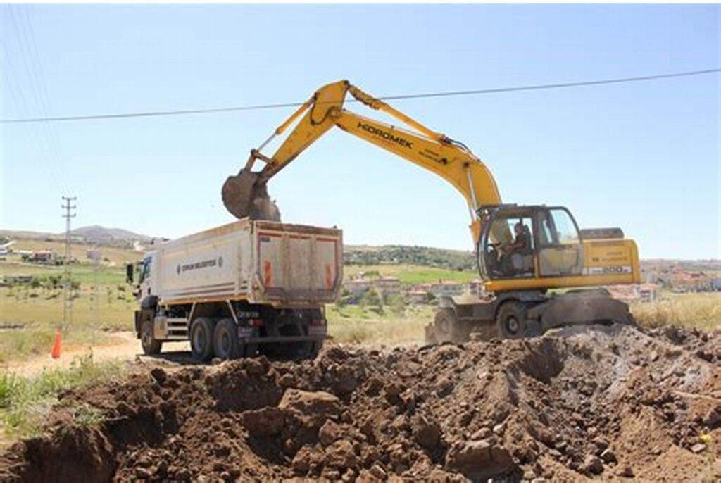 Żółta koparka w trakcie pracy na budowie